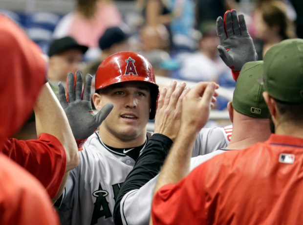 Los Angeles Angels' Mike Trout is congratulated in the dugout after hitting a solo home run during the first inning of an interleague baseball game against the Miami Marlins, Saturday, May 27, 2017, in Miami. (AP Photo/Lynne Sladky) ORG XMIT: FLLS104