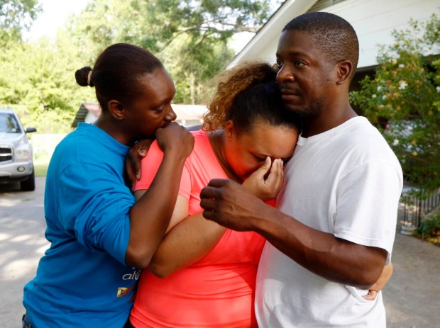 Christianna May-Kelly, center, is supported by family members as she cries after answering reporters questions outside her parents' home in Brookhaven, Miss., Sunday, May 28, 2017. May-Kelly said her parents and mother were among the people gunned down during a shooting in rural Mississippi Saturday night. (AP Photo/Rogelio V. Solis) ORG XMIT: MSRS117