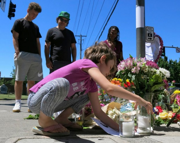 Coco Douglas, 8, leaves a handmade sign and rocks she painted at a memorial in Portland, Ore., on Saturday, May 27, 2017, for two bystanders who were stabbed to death Friday while trying to stop a man who was yelling anti-Muslim slurs and acting aggressively toward two young women. From left are Coco's brother, Desmond Douglas; her father, Christopher Douglas; and her stepmother, Angel Sauls. (AP Photos/Gillian Flaccus) ORG XMIT: RPGF602