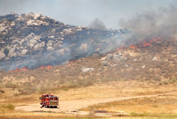 Firefighters approach flames burning near Ironwood Avenue and Moreno Beach Drive in Moreno Valley on May 23, 2017. (Photo courtesy of Dave Toussaint)
