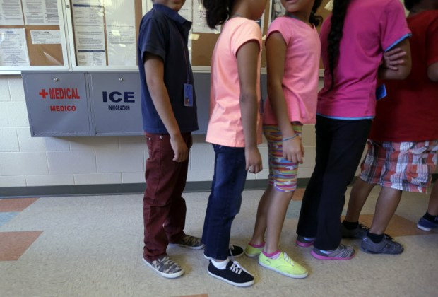 Detained immigrant children line up Sept. 10, 2014, in the cafeteria at the Karnes County Residential Center, a temporary home for immigrant women and children detained at the border, in Karnes City, Texas. A surge of children from Central America arrived at the border without their parents, the result of violence in their home countries. (Eric Gay, The Associated Press)