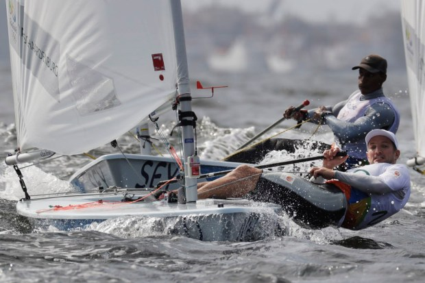 Rutger van Schaardenburf, from the Netherlands, and the Seychelles' Rodney Govinden, background, sail during the Laser men's race at the 2016 Summer Olympics in Rio de Janeiro in August 2016. (File photo by Bernat Armangue, The Associated Press)