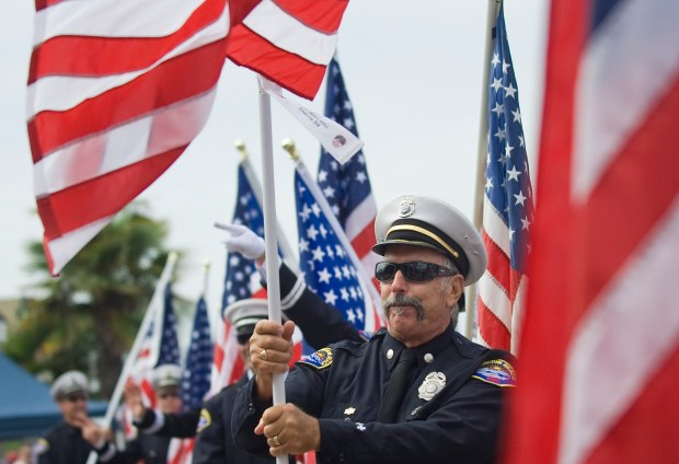Ron Thompson and other firefighters in the Fourth of July Parade carried 343 flags last year to commemorating the firefighters who died during 9/11. / PHOTO MINDY SCHAUER, ORANGE COUNTY REGISTER