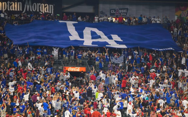 A giant Dodgers flag is unfurled by the Pantone 294 fan club in center field during a Freeway Series game against the Angels at Angel Stadium in June. (Photo by Kevin Sullivan, Orange County Register/SCNG)