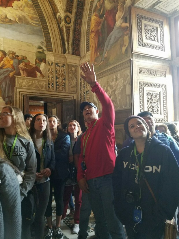 "Teacher Carlos Ayala, center, of Katella High School explains Rafael's ""School of Athens"" in the Vatican's museum during a trip in March 2017 From left, Gracie Pevehouse, Danielle Ayala, Valerie Ayala, Elisabeth Pedersen, Carlos Ayala and Natalie Lopez. (Photo courtesy of Jennifer Ayala)"