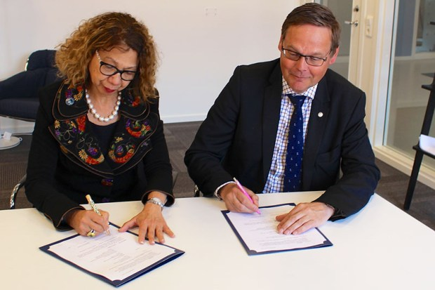 Cal State Fullerton President Mildred García, left, and Johan Sterte, the president of Sweden's Luleå University of Technology, sign agreements for future student exchanges. (Photo courtesy of Cal State Fullerton)