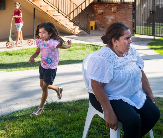 As children swirl around neighbor Yesenia Rojas notes that they always play quietly at her N. Anna Dr., Anaheim, neighborhood on Monday, July 10. In 2012, two fatal police officer involved shootings led to riots, protest and a media zoo in her neighborhood. (Photo by Cindy Yamanaka, Orange County Register/SCNG)