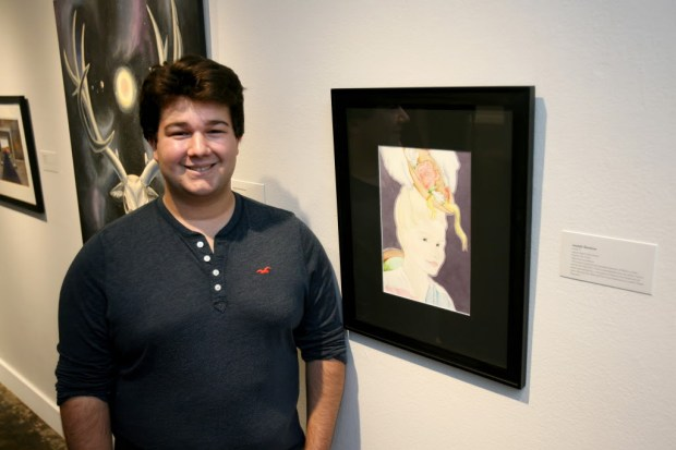 "Laguna Beach High School junior, Joseph Ravenna, poses by his piece during the K-12 LBUSD Summer Art Exhibit at the Laguna Art Museum. Ravenna explains his piece, ""This piece explores the possible election of Marie Le Pen during the May 2017 French presidential race, by which France (here represented by a caricature of Marie Antoinette) would have dawned the National Front and endorsed so-called 'Pastel Populism.'"" (Photo by Ana P. Gutierrez-Garcia, Contributing Photographer)"