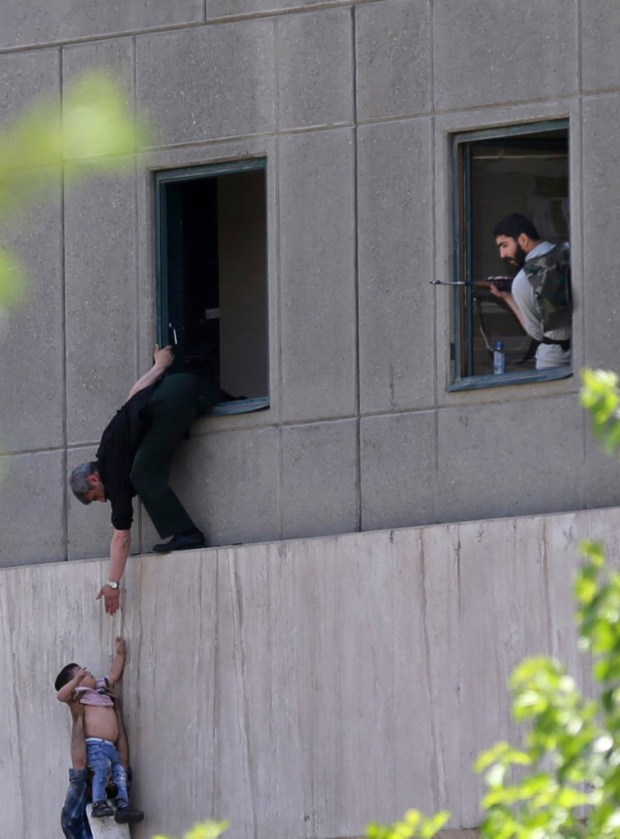 A man hands a child to a security guard from Iran's parliament building after an assault of several attackers, in Tehran, Iran, Wednesday, June 7, 2017. Suicide bombers and gunmen stormed into Iran's parliament and targeted the shrine of Ayatollah Ruhollah Khomeini on Wednesday, killing a security guard and wounding several other people in rare twin attacks, with the siege at the legislature still underway. (Fars News Agency, Omid Vahabzadeh via AP) ORG XMIT: VAH205