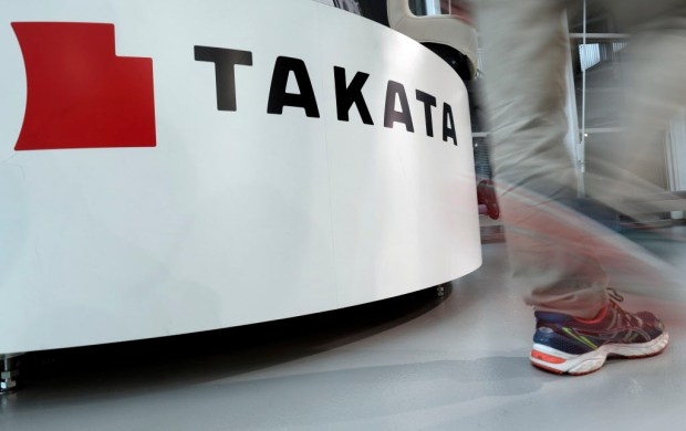 In this May 10 file photo, a visitor walks past the logo of Takata Corp. at a Toyota showroom in Tokyo. Japanese air bag maker Takata Corp. filed for bankruptcy protection in Tokyo on Monday, June 26, 2017 and the U.S., drowned in a sea of lawsuits and recall costs. (AP Photo/Shizuo Kambayashi)
