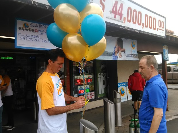 Joseph Zakour, left, and Albeir Alberre put up balloons Sunday, June 11, in front of Marietta Liquor and Deli in Menifee. Alberre owns the store that sold a Powerball ticket that hit a $447 million jackpot Saturday. (Photo by Stephen Wall, The Press-Enterprise/SCNG)