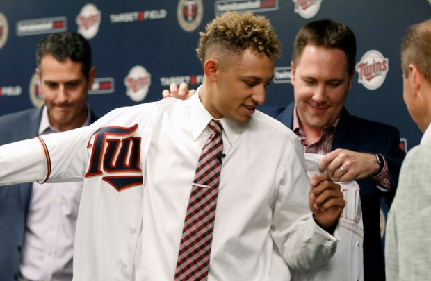 Minnesota Twins chief baseball officer Derek Falvey, left, helps first overall MLB draft pick Royce Lewis into his new jersey as he was introduced to the media between a double-header with the Twins and Cleveland Indians, Saturday, June 17, 2017, in Minneapolis. (AP Photo/Jim Mone) ORG XMIT: MNJM122