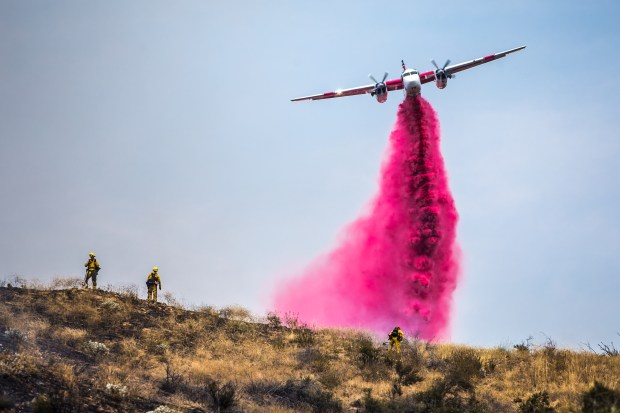 A plane drops fire retardant above a vegetation fire burning near Highway 38 in Mentone on Friday, July 7, 2917. (Photo by Watchara Phomicinda, The Press-Enterprise/SCNG)