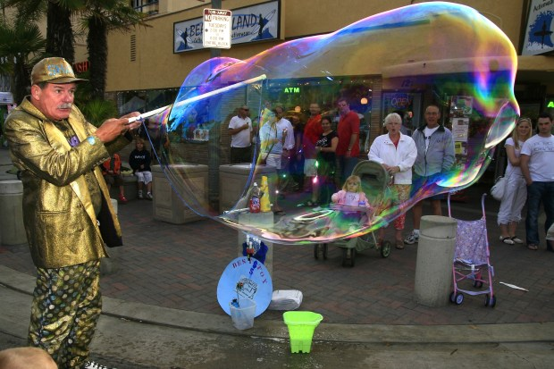 "Street performers such as Bill Ackroyd ""The Bubble Man,"" have helped draw visitors to the Downtown area of Huntington Beach and made Surf City nights a weekly staple. Photo by Mark Martinez/The Register"