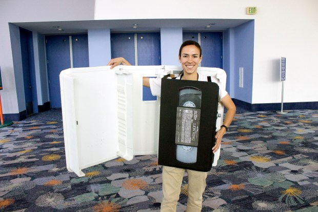 "Kayse Sheppard of Hacienda Heights, shows off how her videocassette case costume opens up to show the actual videocassette for ""The Lion King."" Several members of the Inspiring Women of Imagineering panel were impressed by her ability to contrive and build such an idea. (Photo by Mark Eades, Orange County Register/SCNG)"