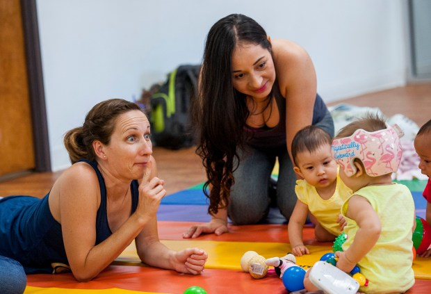 Bethany Peralta, 34, left, and Rosemary Armas, 35, center, work with their babies during a mommy and me class at MOMS Orange County in Santa Ana on Friday, July 14, 2017. (Photo by Paul Rodriguez, Orange County Register/SCNG)