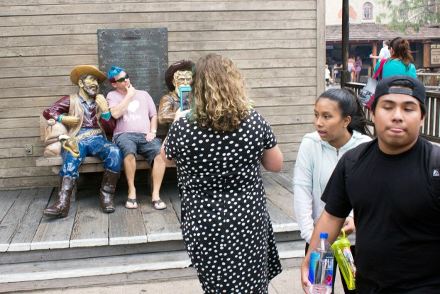 A visitor at Knott's Berry Farm stops to take a photo with her smartphone, forcing others to walk around her. (Photo by Mark Eades, Orange County Register/SCNG)