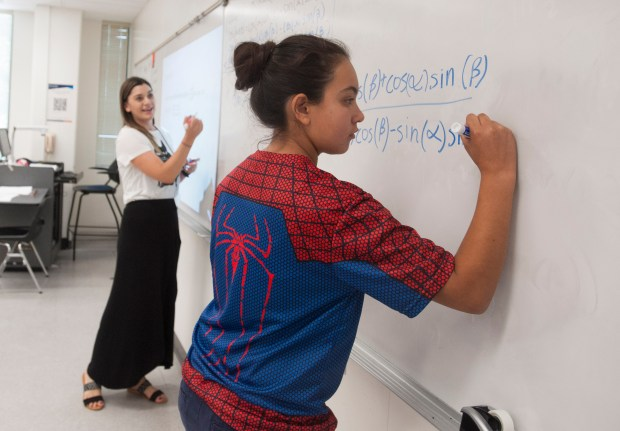 Brigette Reimer, left, an instructor with Project MISS, watches student Anaisabel Chavez as she writes a formula on the white board during a Project MISS session Thursday, July 20, at Cal State Fullerton. (Photo by Sam Gangwer, Orange County Register/SCNG)