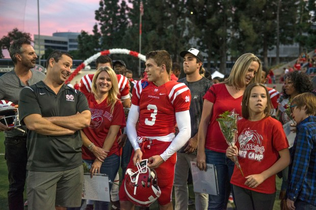 Mater Dei's Chase Ault talks with his family before being announced for senior night during a Trinity League game at Santa Ana Stadium in 2016. . Chase Ault made the training camp roster as a preferred walk-on at UCLA, his dream school, even after Greg Hoyd, of Playing for Envelopes, told him it wouldn't happen. (Photo by Matt Masin, Orange County Register, SCNG)