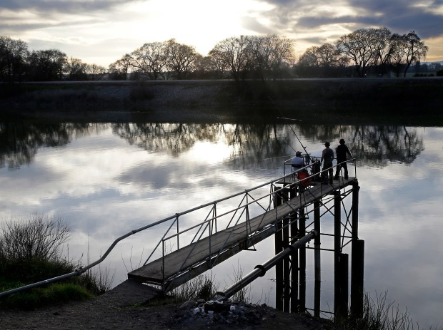 In this Tuesday, Feb. 23, 2016, file photo, people fish along the Sacramento River in the Sacramento-San Joaquin Delta, near Courtland.