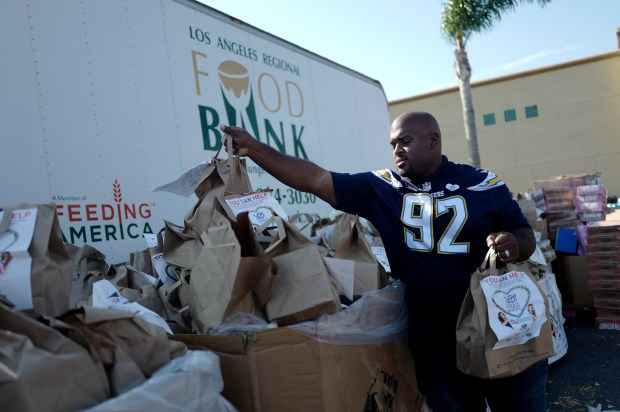 Chargers and former Crenshaw High standout nose tackle Brandon Mebane carries bags of food during ABC7 FeedSoCal food funds drive for the Los Angeles Food Bank in the Albertsons Parking lot in Gardena, Calif., on Friday, June 23, 2017 in Los Angeles. (Photo by Keith Birmingham, Pasadena Star-News/SCNG)