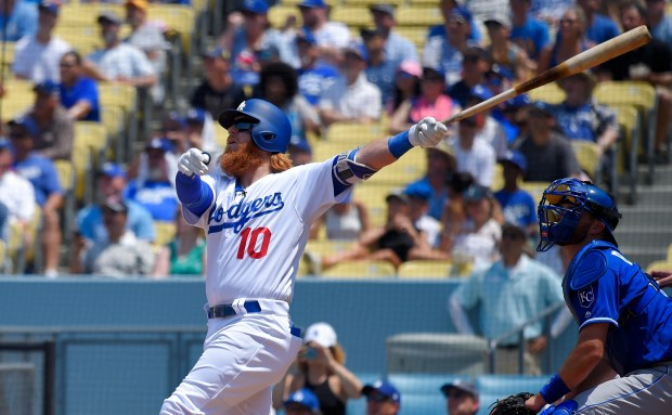 Los Angeles Dodgers' Justin Turner, left, hits a two-run home run as Kansas City Royals catcher Drew Butera watches during the third inning of a baseball game, Sunday, July 9, 2017, in Los Angeles. (AP Photo/Mark J. Terrill) ORG XMIT: LAD113