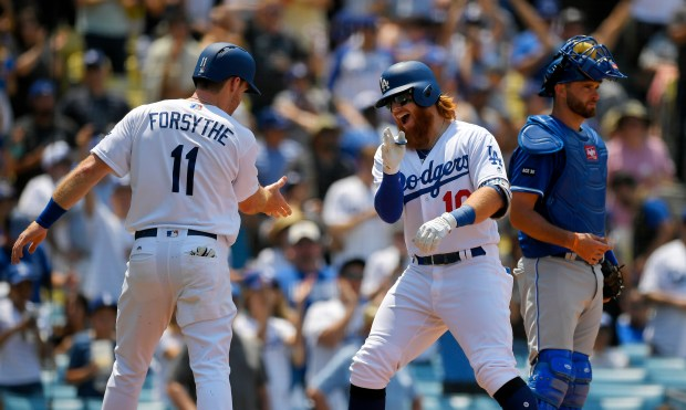 Los Angeles Dodgers' Justin Turner, center, celebrates with Logan Forsythe, left, after hitting a two-run home run as Kansas City Royals catcher Drew Butera looks on during the third inning of a baseball game, Sunday, July 9, 2017, in Los Angeles. (AP Photo/Mark J. Terrill) ORG XMIT: LAD114