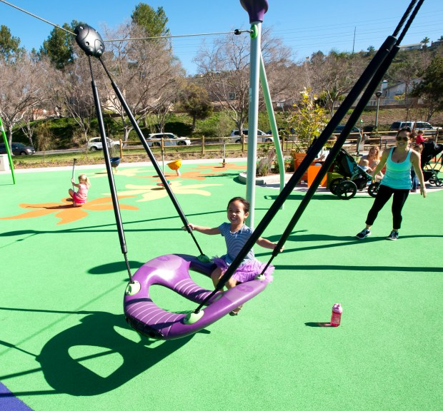 """Jenavieve Cao, 4, of Las Flores, gets a push from Katie Nguyen at Pavion Park in Mission Viejo.///ADDITIONAL INFO: 06.s.mv.pavion_park.0212.db.jpg -- 2/9/15 -- PHOTO BY DAVID BRO, CONTRIBUTING PHOTOGRAPHER----The City of Mission Viejo has renovated Pavion Park with what designers call """"Universal"""" access for kids of all ages and abilities including adults."""