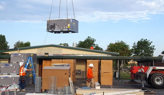 An air-conditioning unit is lowered into Rosita Elementary School in Santa Ana this summer. The Garden Grove Unified School District is in the middle of a years-long process to add air conditioning in all of its facilities. (Courtesy of Abby Milone, Garden Grove Unified School District.)