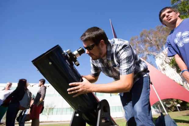 Joshua Smith, associate professor of physics at CSUF, looks through a telescope during a solar eclipse in 2014. (Photo courtesy of Cal State Fullerton)