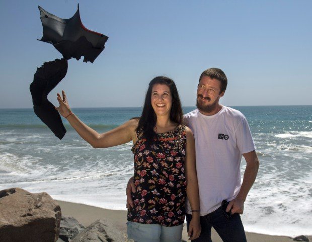 Shark attack victim Leeanne Ericson, with her boyfriend Dusty Phillips, with her wetsuit that was shredded by a shark on April 29th. She keeps an upbeat attitude even as she faces a long road of recovery. She is pictured in Capistrano Beach on Wednesday, August 30, 2017. Ericson says she is still not ready to visit San Onofre State Beach where the attack occurred. (Photo by Mindy Schauer, Orange County Register/SCNG)