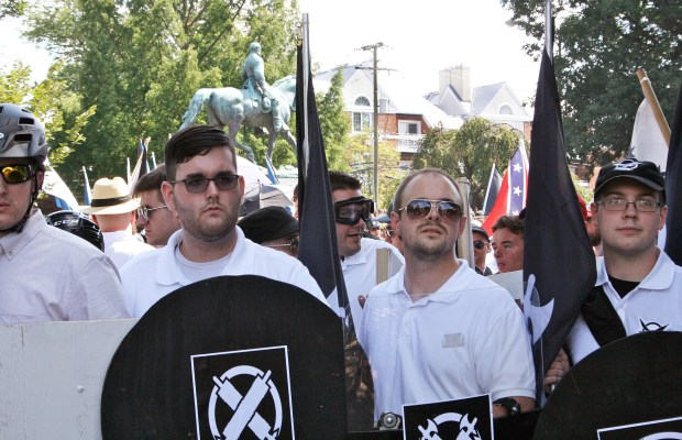 In this Saturday, Aug. 12, 2017 photo, James Alex Fields Jr., second from left, holds a black shield in Charlottesville, Va., where a white supremacist rally took place. Fields was later charged with second-degree murder and other counts after authorities say he plowed a car into a crowd of people protesting the white nationalist rally. (Alan Goffinski via AP)