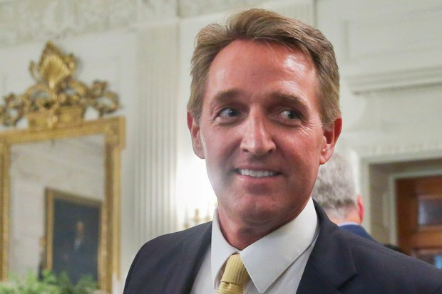 In this July 19 photo, Sen. Jeff Flake, R-Ariz. walks to his seat as he attends a luncheon with other GOP Senators and President Donald Trump at the White House in Washington.  Bombarded by the sharpest attacks yet from fellow Republicans, President Donald Trump on Thursday, Aug. 17, 2017, dug into his defense of racist groups by attacking members of own party and renouncing the rising movement to pull down monuments to Confederate icons. (AP Photo/Pablo Martinez Monsivais)