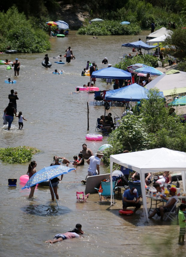 Hundreds of people cool off in the Santa Ana River with their popups and lawn chairs to sit in the river and cool off near the corner of 64th and Downey streets where is parking and an access trial to the river Sunday in Jurupa Valley, CA. August 6, 2017. (TERRY PIERSON,THE PRESS-ENTERPRISE/SCNG)