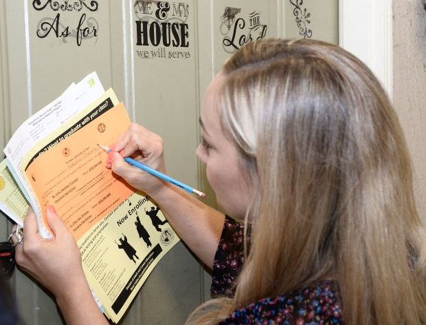 Megan Brown writes information on a form that she left at the door of a home where a truant student lives. Brown traveled around the Valley as part of the district's during Student Recovery Day.