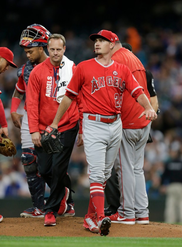 Los Angeles Angels starting pitcher Andrew Heaney leaves the baseball game with a trainer during the third inning against the Seattle Mariners, Saturday, Sept. 9, 2017, in Seattle. (AP Photo/John Froschauer)