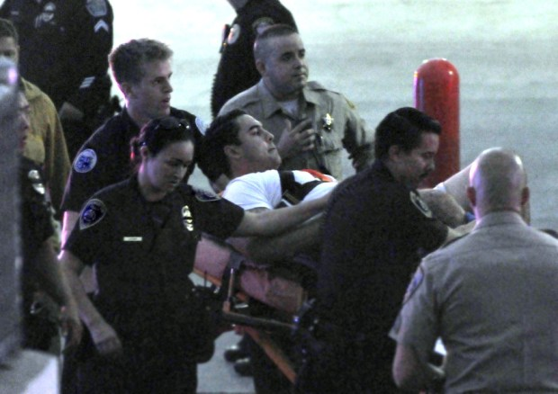 Paramedics and fellow officers rush a Hawthorne police officer to a nearby ambulance after he was shot during an altercation with someone at a public storage building in the 4800 block of west Rosecrans Ave., Hawthorne, just after sundown, Saturday November 19, 2016. (Mike Mullen photo)