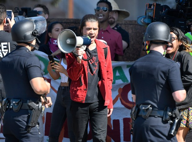 A protester shouts at cops with a bullhorn on Wilshire Boulevard, outside the Federal Building in Westwood, as DACA supporters square off with LAPD on deadline day for DACA renewals. (File photo by John McCoy, Los Angeles Daily News/SCNG)