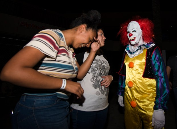 Rachel Green, 16, of Redlands, tries not to make eye contact with a scary clown at Spalsh Kingdom during a preview of two of the mazes for the water park's first-ever ZombiEmpire. The waterpark will be transformed into a safe haven from zombies which are occupying mazes on site. October 5, 2017. (Photos by Frank Perez)