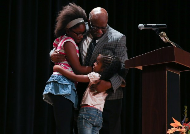 Lee. A Mitchell, Jr. hugs his grandchildren during the plaque dedication ceremony. The Norwalk-La Mirada Unified School District dedicates a plaque to Lee Mitchell, a retired band director and the first African-American teacher in the district on Saturday, Oct. 14, 2017. (Photo by Shilah Montiel for SCNG)