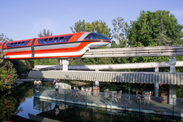 The Disneyland Monorail, which opened in 1959 as the Disneyland-Alweg Monorail, sweeps over the waterway that once held the Motorboat Cruise attraction in Fantasyland. When Alweg dropped its sponsorship in 1983, Disney dropped it from the name. //// ADDITIONAL INFORMATION: From 1980 to 1989, major changes and additions were made to Disneyland. - Date of photo: VARIOUS - disney.bydecade.1970s -- Photo by: VARIOUS