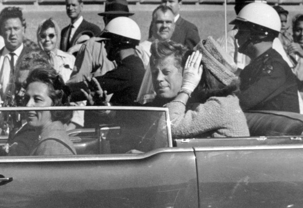 In this Nov. 22, 1963 file photo, President John F. Kennedy waves from his car in a motorcade in Dallas. Riding with Kennedy are First Lady Jacqueline Kennedy, right, Nellie Connally, second from left, and her husband, Texas Gov. John Connally, far left. The National Archives released the John F. Kennedy assassination files on Thursday, Oct. 26, 2017. (AP Photo/Jim Altgens, File)