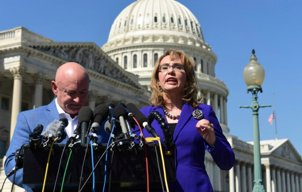 Former Rep. Gabrielle Giffords, D-Ariz., right, standing with her husband Mark Kelly, left, speaks on Capitol Hill in Washington, Monday, Oct. 2, 2017, about the mass shooting in Las Vegas. Giffords, was a congresswoman when she was shot in an assassination attempt in 2011. (AP Photo/Susan Walsh)