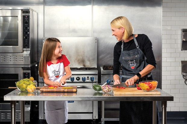 Emma Scott, 6, a student with Culinary Kids shares a laugh with her mother and Culinary Kids instructor, Anne Fluor Scott, at The Hood Kitchen Space in Costa Mesa works in the kitchen on Thursday, September 21, 2017. Cooking with your kids encourages them to eat healthier and learn to cook for themselves. Culinary Kids is a program that helps kids learn to cook at a young age. (Photo by Leonard Ortiz, Orange County Register/SCNG)