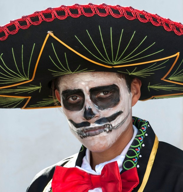 "Eli Cruz, of Santa Ana, dresses as Day Of the Dead mariachi at the first annual ""Viva la Vida"" festival at the Santa Ana Train Station on Sunday. ///ADDITIONAL INFO: - Day.of.the.dead.train.1102- shot 110115 - ANA VENEGAS, ORANGE COUNTY REGISTER The first annual ""Viva la Vida"" festival was a celebration of Day of the Dead (Dia De Los Muertos) at the Santa Ana Train Station. The event featured individual alters to ancestors, food and entertainment."