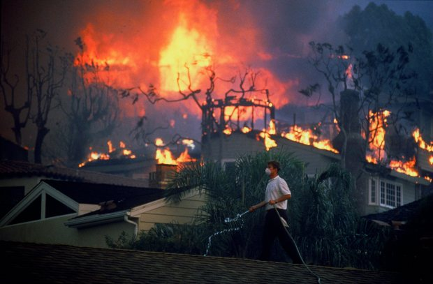 While firefighters line the streets of Laguna Beach, a resident tries to save his home using a garden hose to keep roof wet. (Photo by Bruce R. Strong, Orange County Register/SCNG)