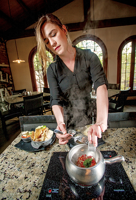 Server Hannah Bolig makes s Sun-dried Formaggio with basil pesto, beer and garlic at Rok N Fondue Restaurant in Redlands, Sept. 12, 2017. (Eric Reed/Redlands Magazine)