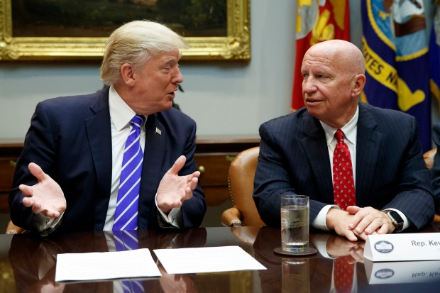 Rep. Kevin Brady, R-Texas, right, listens as President Donald Trump speaks during a meeting with members of the House Ways and Means committee in the Roosevelt Room of the White House, Tuesday, Sept. 26, 2017, in Washington. (AP Photo/Evan Vucci)