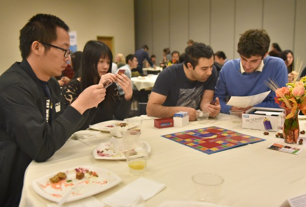 Yongzan Zheng and Kaizhu Guo from China, Ali Ghohremannnezhad from Iran and Gianluca Bianchin from Italy play Pictionary at a Tuesday, Nov. 21, Thanksgiving meal for UC Riverside international students.