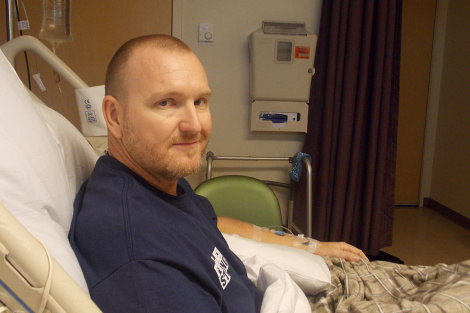 """Kurt Fowler has health insurance through his jobs as a firefighter from Lake Havasu City, Ariz. But he doesn't know what out-of-pocket medical costs he may face from the shooting. """"Medical expenses are astronomical these days,"""" he said from a hospital bed at Sunrise Hospital & Medical Center. (Anna Gorman/KHN)"""